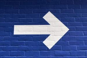White Painted Arrow on a Blue Brick wall